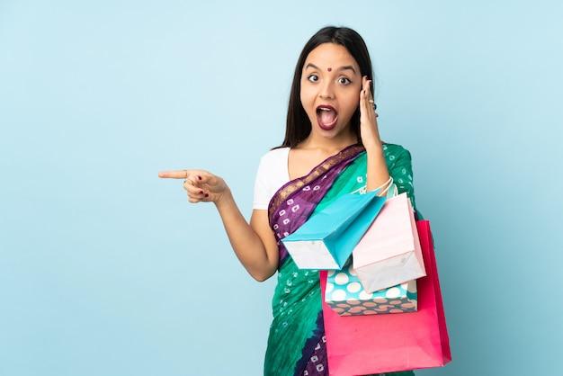 Jeune femme indienne avec des sacs à provisions surpris et pointant le doigt sur le côté