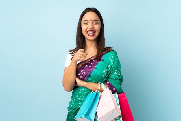 Jeune femme indienne avec des sacs à provisions surpris et pointant