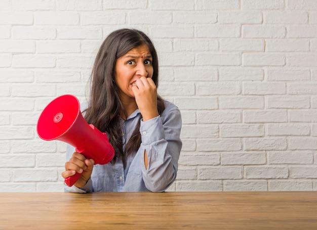 Jeune femme indienne se ronger les ongles, nerveuse et très anxieuse et inquiète pour l'avenir
