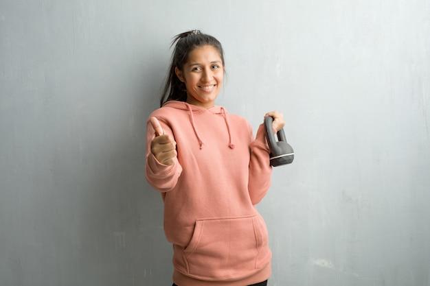 Jeune femme indienne sportive contre un mur gai et excité