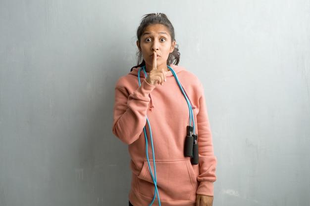Jeune femme indienne sportive contre un mur gardant un secret ou demandant le silence, visage sérieux.