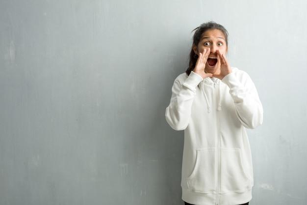 Jeune femme indienne sportive contre un mur de gymnase hurlant de joie, surprise par une offre ou une promotion