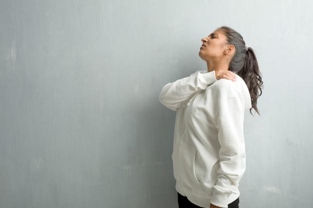 Jeune femme indienne sportive contre un mur de gymnase avec maux de dos dus au stress au travail, fatigués et astucieux