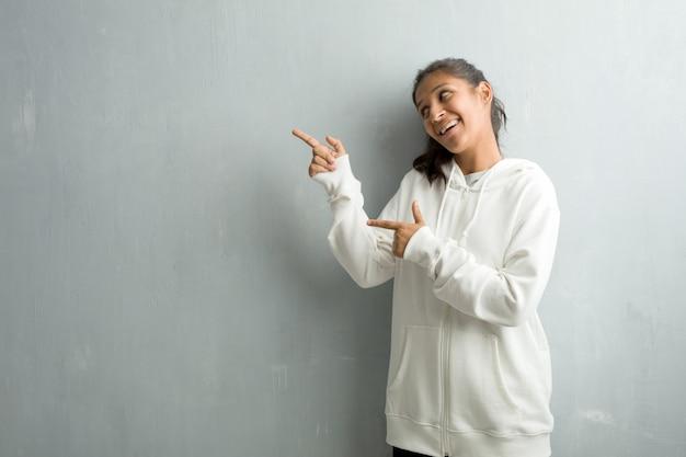 Jeune femme indienne sportive contre un mur de gymnase pointant vers le côté