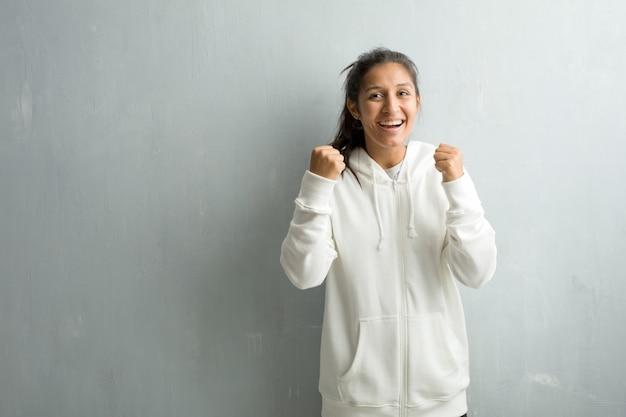 Jeune femme indienne sportive contre un mur de gymnase très heureux et excité