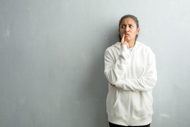 Jeune femme indienne sportive contre un mur de la salle de gym doutant et confus, pensant à une idée ou inquiet pour quelque chose