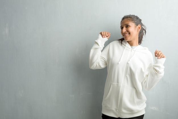 Jeune femme indienne sportive contre un mur de la salle de gym écouter de la musique