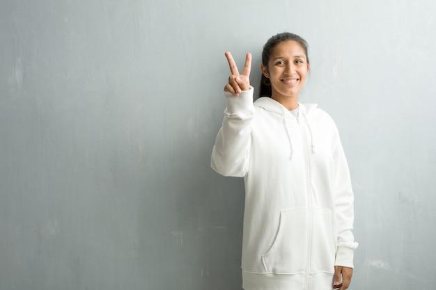 Jeune femme indienne sportive contre un mur de la salle de sport montrant le numéro deux
