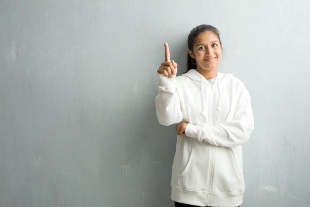 Jeune femme indienne sportive contre un mur de la salle de sport montrant le numéro un, symbole de comptage