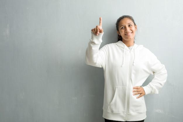 Jeune femme indienne sportive contre un mur de la salle de sport montrant le numéro un