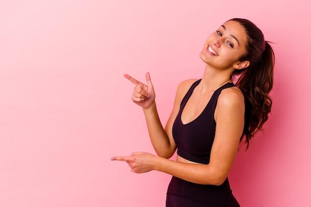 Jeune femme indienne sportive isolée sur fond rose excité pointant avec les index loin.