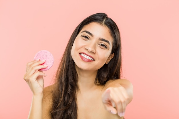 Jeune femme indienne tenant un disque de soins de la peau du visage sourires joyeux pointant vers l'avant.