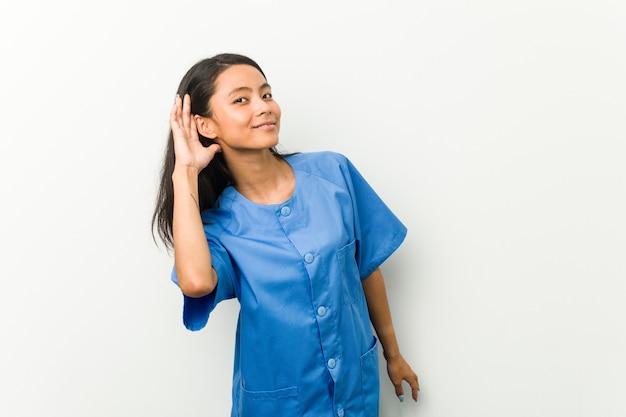 Jeune femme infirmière asiatique essayant d'écouter un potin