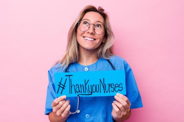 Jeune femme infirmière australienne tenant une pancarte de la journée internationale des infirmières isolée sur fond bleu