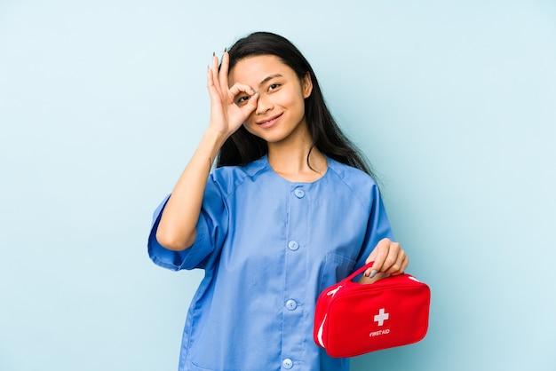 Jeune femme infirmière chinoise isolée sur un mur bleu en gardant un secret ou en demandant le silence