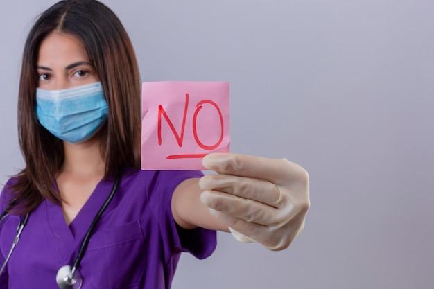 Jeune femme infirmière portant des gants de masque de protection d'uniforme médical et avec stéthoscope montrant le papier de rappel avec mot pas à la confiance