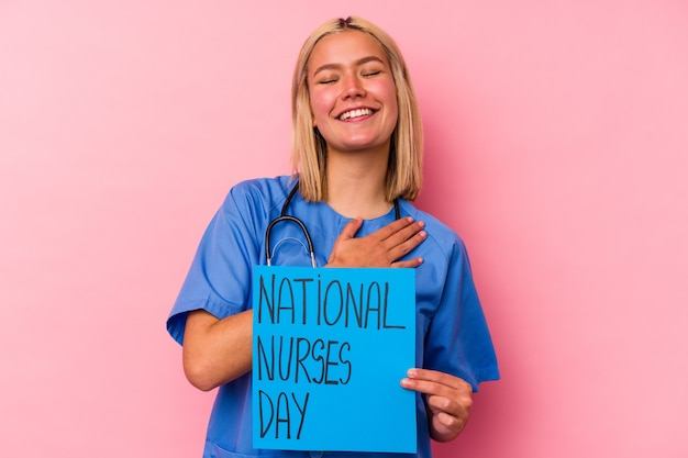 Jeune femme infirmière tenant une bannière de femme infirmières internationales isolée sur mur rose