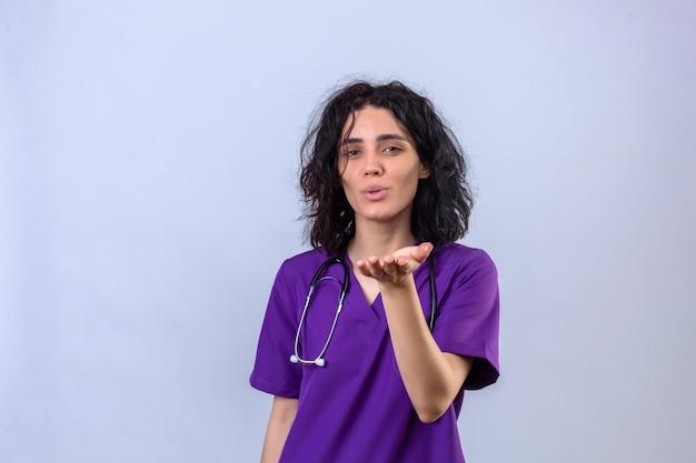 Jeune femme infirmière en uniforme médical et avec stéthoscope soufflant un baiser avec la main sur l'air étant belle debout
