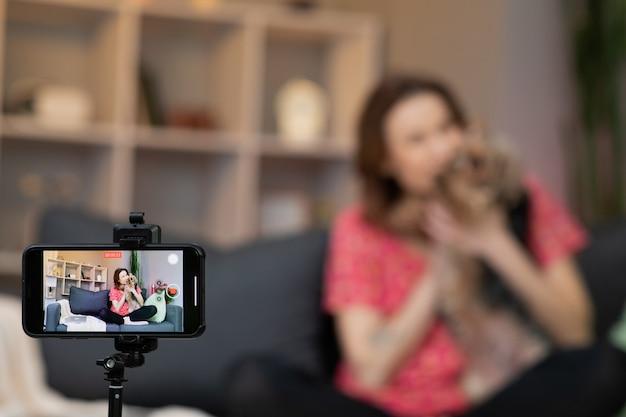 Jeune femme influenceuse vlogger s'asseoir à la maison en parlant en regardant la caméra et en faisant un enregistrement d'appel vidéo conférence.