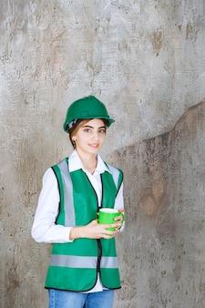 Jeune femme ingénieur portant un gilet vert et tenant une tasse de café