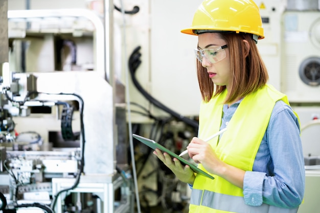 Jeune femme ingénieur vérifie la machine et l'équipement dans l'usine d'automatisation.