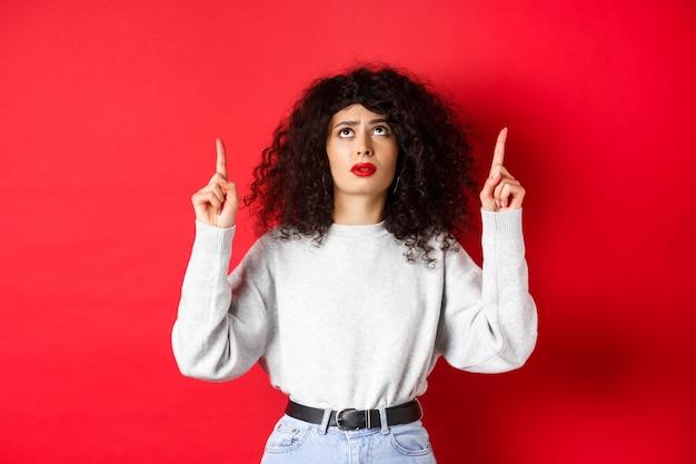 Jeune femme inquiète aux cheveux bouclés, fronçant les sourcils et semblant douteuse, pointant vers le haut avec un visage hésitant ou inquiet, debout sur fond rouge.