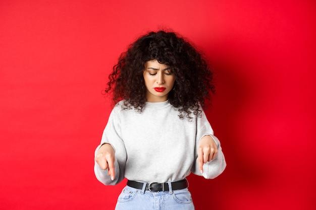 Jeune femme inquiète avec une coiffure frisée, regardant vers le bas et pointant vers l'espace vide avec un visage hésitant concerné, debout sur fond rouge