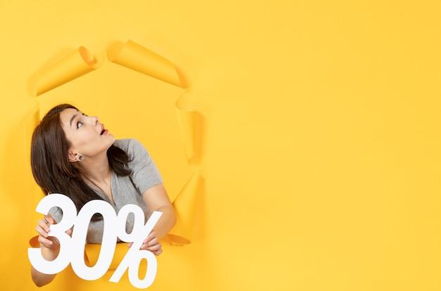 Jeune femme avec inscription signe sur fond de papier jaune déchiré argent vente shopping