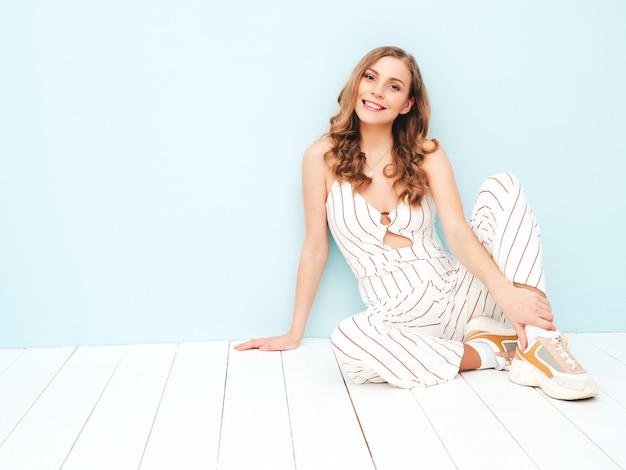 Jeune femme insouciante assise près d'un mur bleu clair en studio