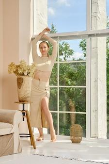 Jeune femme insouciante debout près de la fenêtre à la maison le week-end