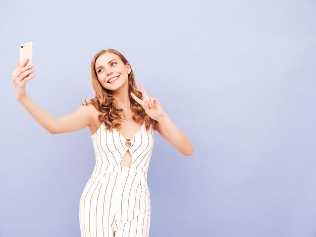 Jeune femme insouciante posant près du mur violet en studio