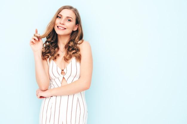 Jeune femme insouciante posant près d'un mur bleu clair en studio