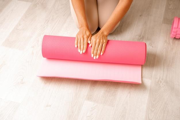 Jeune femme avec un instructeur de fitness aux cheveux longs en vêtements de sport beige se préparant à l'étirement et