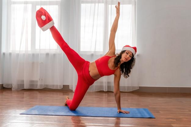 Une jeune femme instructeur de fitness en bonnet de noel et leggings sportswear rouge et haut qui s'étend dans le