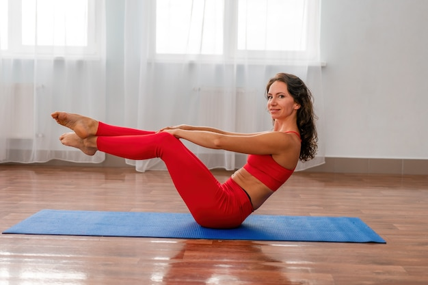 Une jeune femme instructeur de fitness en leggings sportswear rouges et haut s'étirant dans la salle de sport devant elle