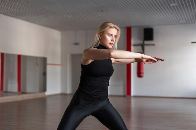 Jeune femme instructeur de fitness en vêtements élégants noirs montre comment garder l'équilibre debout dans la salle de sport
