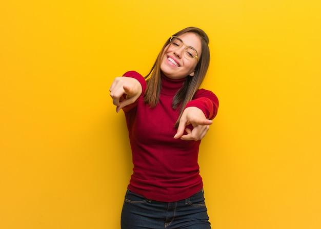 Jeune femme intellectuelle joyeuse et souriante pointant vers l'avant