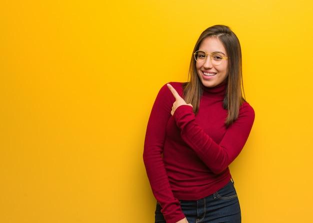 Jeune femme intellectuelle souriante et pointant sur le côté