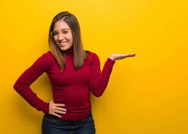 Jeune femme intellectuelle tenant quelque chose avec la main