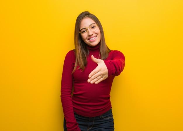 Jeune femme intellectuelle tendre la main pour saluer quelqu'un