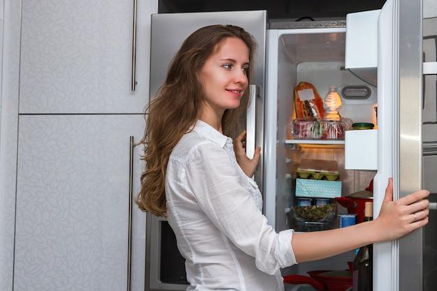 Jeune femme à l'intérieur dans la cuisine ouvrant la porte du réfrigérateur et regardant joyeusement la porte du réfrigérateur