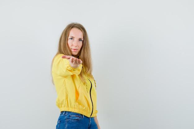 Jeune femme invitant à venir en blouson aviateur jaune et jean bleu et à la recherche de sérieux. vue de face.