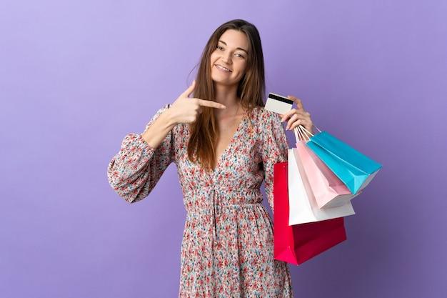 Jeune femme d'irlande isolée sur fond violet tenant des sacs et une carte de crédit
