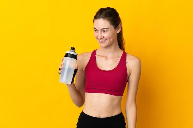 Jeune femme d'irlande isolée sur mur jaune avec bouteille d'eau de sport