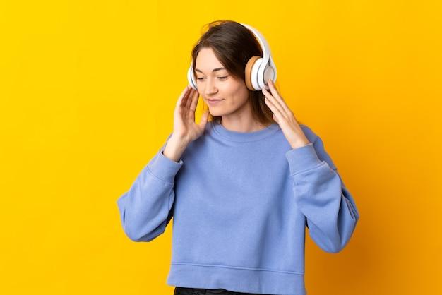 Jeune femme d'irlande isolée sur un mur jaune à l'écoute de la musique