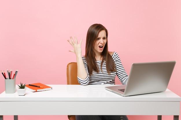 Jeune femme irritée en colère écartant la main travaillant sur un projet alors qu'elle était assise au bureau avec un ordinateur portable