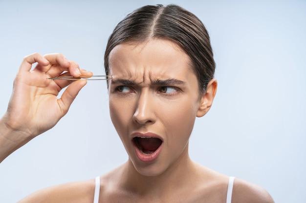 Jeune femme irritée effectuant une procédure de beauté