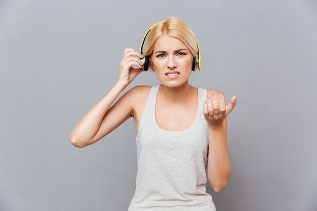 Jeune femme irritée en fronçant les sourcils enlevant des écouteurs sur un mur gris