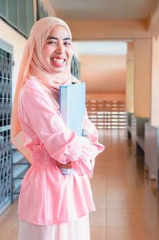 Jeune femme islamique. elle est debout sur un balcon dans le bureau. elle est sourire et tenant document