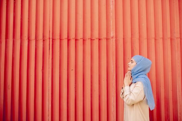 Jeune femme islamique en tenue décontractée et hijab debout contre le mur rouge en priant ou en méditant